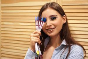 belle fille avec du maquillage bleu couvre son visage avec des ongles de palette photo