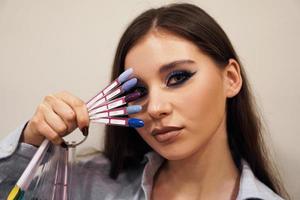 belle fille couvre son visage avec une palette avec des ongles photo