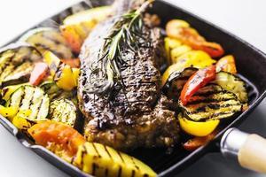 steak d'agneau bio grec avec légumes grillés et herbes dans une poêle grésillante photo