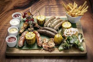 Plateau de viande barbecue mixte bio plateau de viande rustique avec saucisses, brochettes, plats d'accompagnement et sauces photo