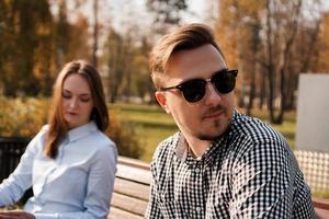 Jeune couple en querelle assis sur un banc dans le parc photo