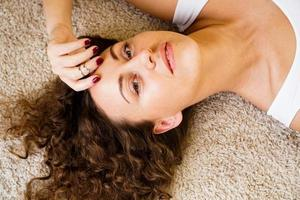 femme allongée sur un tapis, heureuse jeune fille adulte allongée sur le sol photo