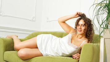 femme en lingerie blanche assise sur un canapé vert à la maison - matin heureux photo