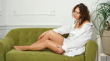 femme aux longues jambes sur un canapé vert. concept de santé et de soins des pieds photo