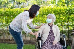 aider une femme âgée asiatique sur un fauteuil roulant électrique photo