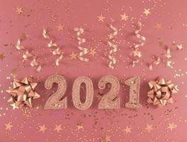chiffres scintillants 2021, étoiles, arcs et rubans sur fond rose. photo