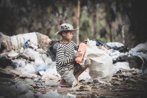 pauvre garçon ramassant des ordures dans son sac pour gagner sa vie. photo