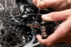 serrage du câble de changement de vitesse sur un vélo avec multitool. photo