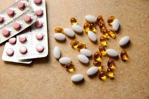 blister avec des comprimés roses et de la vitamine d et des capsules avec de l'huile de poisson se trouvent de manière chaotique dans le contexte d'un comptoir de sable photo
