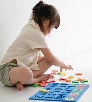 petite fille jouant avec un puzzle alphabet photo