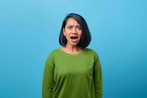 femme asiatique choquée avec la bouche ouverte sur fond bleu photo