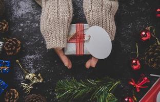 main tenant une boîte-cadeau noire sur un fond de plâtre noir photo