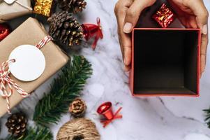 une main tenant une boîte-cadeau noire sur un sol en ciment blanc photo