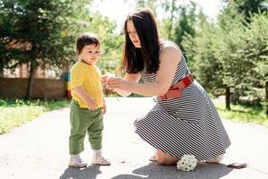 mère promenant sa fille dans le parc en lui donnant des fleurs photo