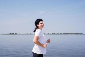 Rire actif femme senior jogging près de la rivière photo