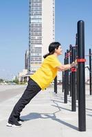 Smiling senior woman doing push ups à l'extérieur sur les bars du terrain de sport photo