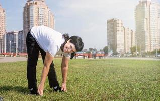 smiling senior woman warming stretching à l'extérieur dans le parc photo