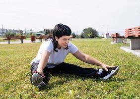 femme souriante, échauffement, étirement, séance, herbe, dans parc photo