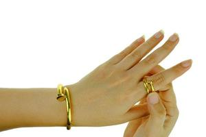 main de femme avec un bracelet en or et des bijoux en bague photo