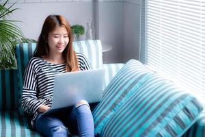 belle de portrait jeune femme asiatique utilisant un ordinateur portable pour les loisirs sur un canapé dans le salon, fille travaillant en ligne avec un ordinateur portable indépendant avec un concept d'entreprise de communication heureux. photo