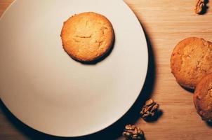 vue de dessus des biscuits aux noix, sur une assiette blanche et une table en bois photo
