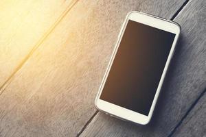téléphone intelligent sur le fond d'écran en bois photo