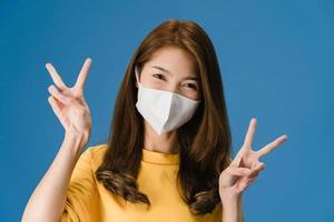 jeune fille asiatique porte un masque facial montrant un signe de paix sur fond bleu. photo