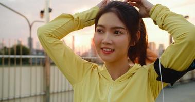 Dame athlète asiatique en vêtements jaunes se préparant à l'entraînement en milieu urbain. photo