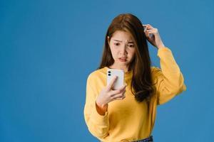 pensant rêver jeune femme asiatique utilisant un téléphone sur fond bleu. photo