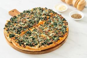 pizza aux épinards et au fromage sur plateau en bois photo