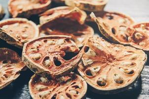 herbes séchées et fruits de bael séchés, tranches de fruits de bael sur table. photo