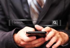 main d'affaires utilisant un smartphone avec la technologie de recherche de données photo