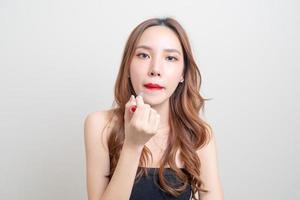 portrait belle femme maquillage et à l'aide de rouge à lèvres rouge photo