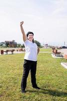 femme en vêtements de sport faisant de l'exercice dans le parc debout avec les bras levés photo