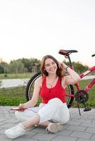 adolescente assise à côté de son vélo dans le parc en écoutant de la musique photo