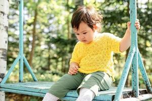 triste petite fille assise sur la balançoire photo