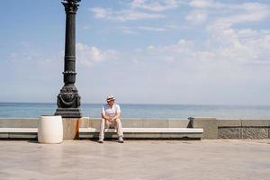 jeune homme assis sur le banc au bord de la mer photo