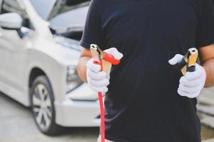 mécanicien automobile tenant des câbles de démarrage pour charger la batterie de voiture photo