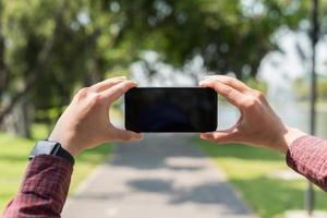 gros plan des mains masculines tenant un smartphone pour prendre une photo. photo