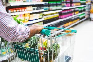 jeune homme, faire du shopping au supermarché. photo