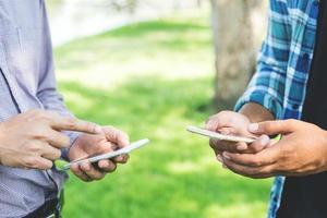 deux hommes d'affaires utilisant un smartphone dans le parc. photo
