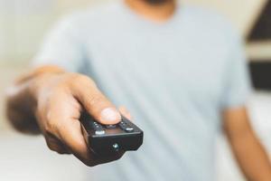 homme de main tenant la télécommande de la télévision. photo