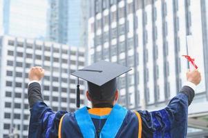 heureux diplômé. Heureux homme asain en robes de graduation titulaire d'un diplôme photo