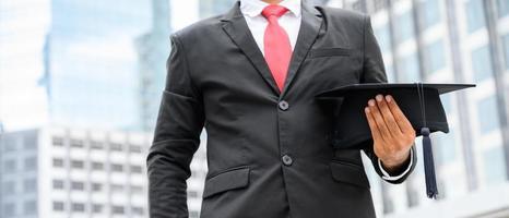 Close up businessman holding graduation cap à la main photo