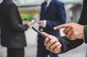 les groupes d'entreprises utilisent des téléphones portables pour établir des contacts d'affaires photo