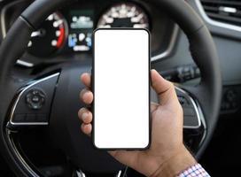 main tenant l'écran vide du smartphone tout en conduisant la voiture. photo