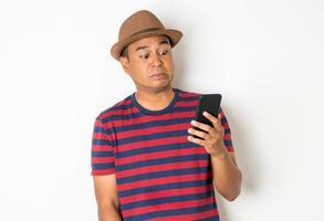 homme choqué à l'aide de téléphone sur fond blanc photo