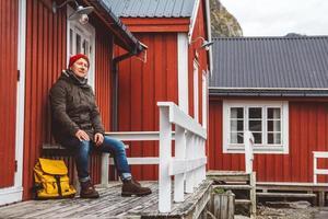 l'homme voyageur est assis près d'une maison en bois de couleur rouge photo