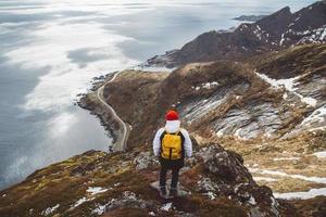 homme avec un sac à dos debout sur fond de montagnes et de mer photo