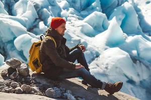 homme voyageur assis sur un rocher sur fond de glacier et de neige photo